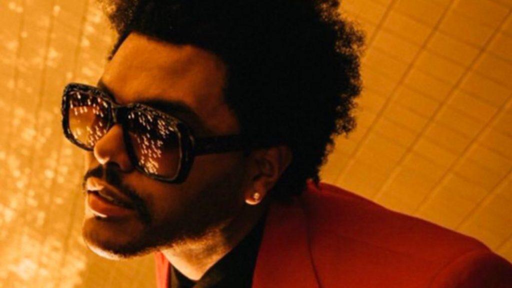 The Weeknd no videoclipe de blinding lights com óculos escuros e terno vermelho