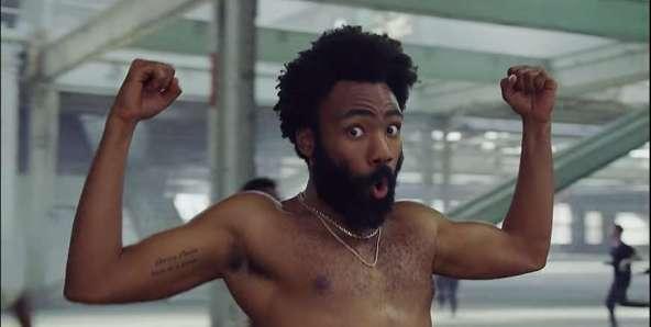 Donald Glover no clipe de This Is America, olhando para a câmera enquanto flexiona os bíceps.