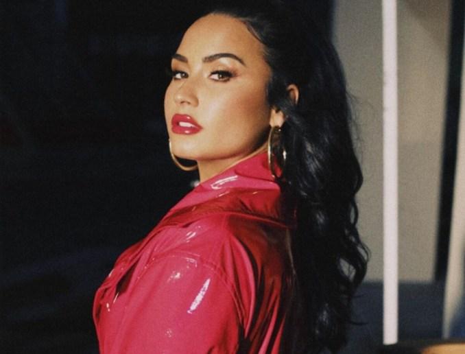 Demi Lovato e Selena Gomez já pensaram em parar de fazer música. Na foto, Demi está de perfil usando um casaco de couro rosa, uma argola no ouvido e o cabelo preso em rabo de cavalo