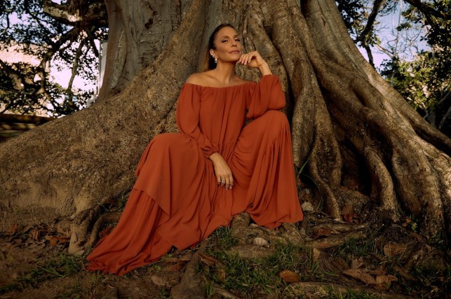 Atração musical final do programa bbb. Ivete Sangalo sentada em frente a uma árvore e vestindo um vestido vermelho.