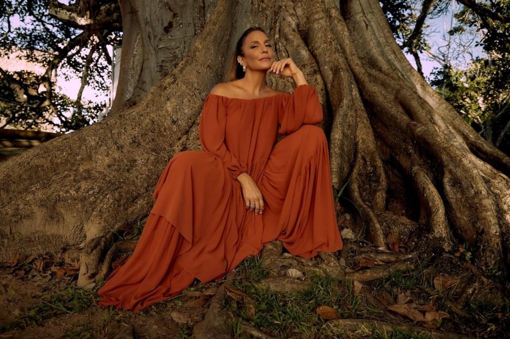 Ivete Sangalo sentada em frente a uma árvore usando um vestido vermelho.