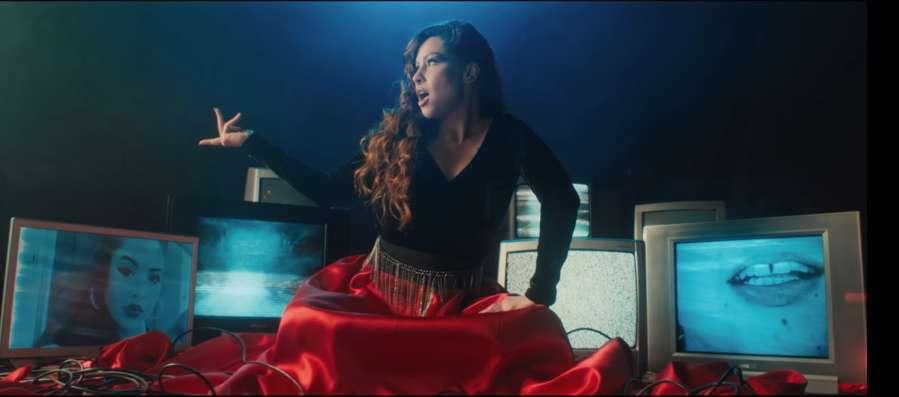 Pitty no clipe de Na Tela, sentada no chão, com uma saia longa vermelha que se espalha no chão e com várias TVs ao fundo, mostrando rostos, bocas e ruídos brancos.