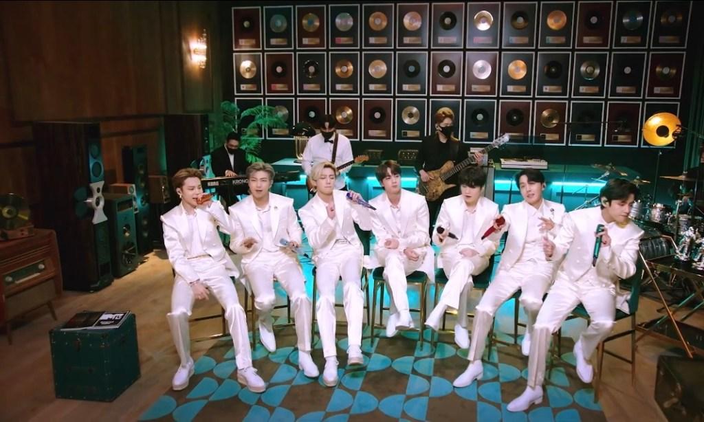 Todos usando terno branco, sentados em um banquinho, com a banda atrás. Na parede pregado vários quadros de vinil