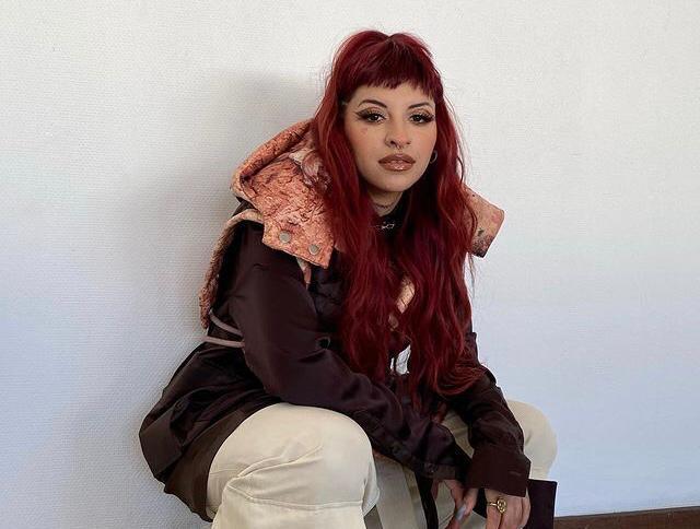 cazzzu arista latina usando uma casaco marrom, calça branca, cabelo vermelho e agachada