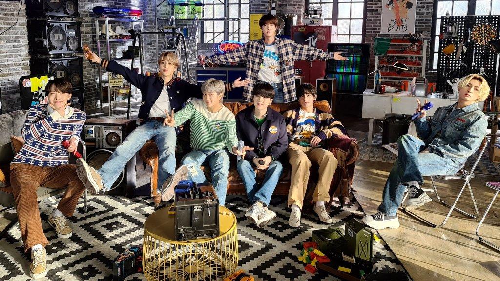 BTS em uma sala playground com vários jogos ao redor dos integrantes como pebolim, cesta de basquete, moto. 4 integrantes sentados no sofá de couro marrom, um em pé com os braços abertos atrás do sofá, outro em uma poltrona e outro em uma cadeira.