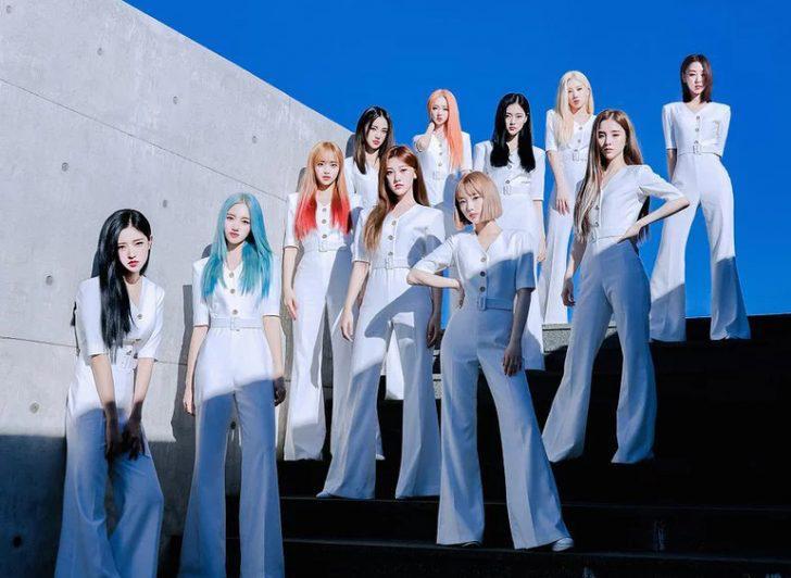Grupo loona de k-pop retirado do spotify 11 integrantes em pé em uma escada vestindo uma calça branca de seda comprida e uma blusa branca