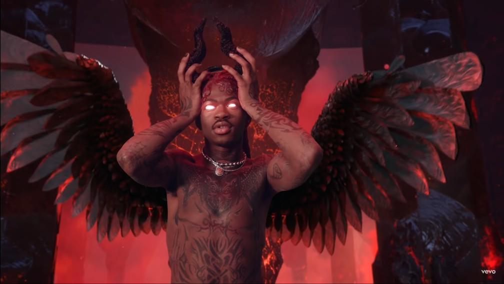 """A imagem apresenta o cantor Lil Nas X, que foi acusado de plágio, no clipe de """"Montero (Call Me By Your Name)"""". Lil Nas aparece numa espécie de inferno e pode ser visto da cabeça até a cabeça com um par de asas vermelho e preto. Seus olhos brilham na cor vermelha e o cantor está com as mãos segurando um par de chifres pretos."""