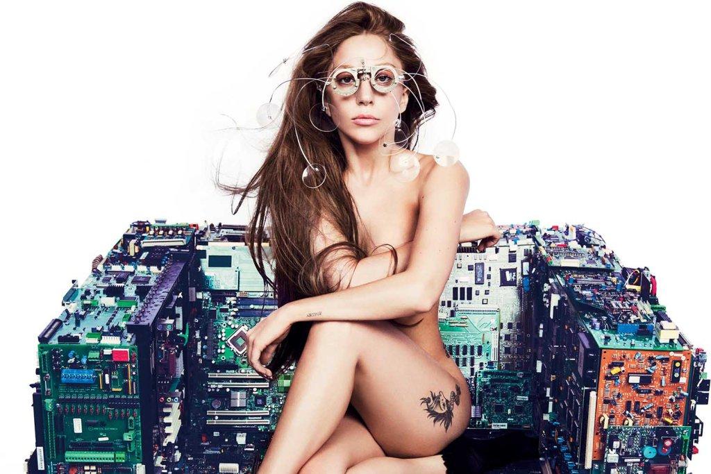 """Lady Gaga sentada, nua, em uma cadeira feita de materiais eletrônicos, usando um óculos e com cabelos castanhos. A foto estampa a matéria """"Por que """"ARTPOP"""", da Lady Gaga, voltou à lista dos mais vendidos?"""""""