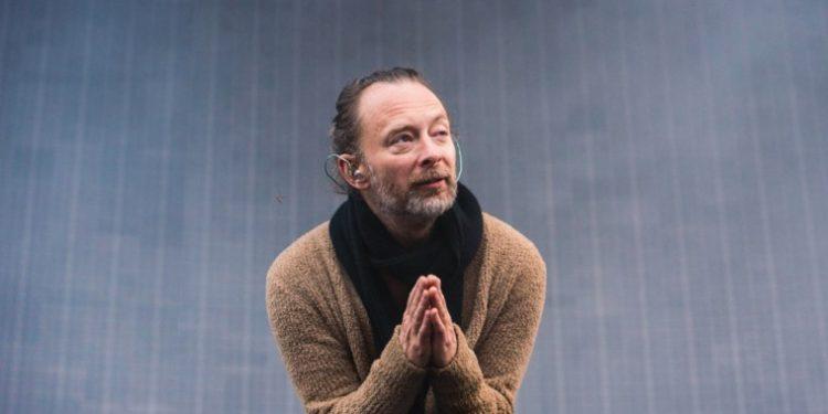 Thom Yorke é um dos artistas que critica plataformas de streamings. Na foto, ele aparece usando um casaco marrom e uma echarpe preta no pescoço, com as mãos juntas em formato de oração.