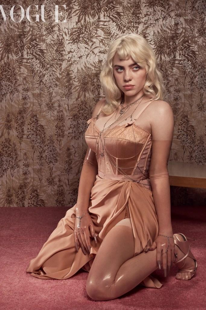 """Billie Eilish aparece vestida com um espartilho marrom, ajoelhada em um tapete cor de barro. Ela olha para o lado direito. Billie está com o cabelo loiro. Sua mão direita está à sua frente e a esquerda perto dos seus pés. A imagem estampa a matéria """"Billie Eilish na Vogue UK: 3 destaques da entrevista da cantora"""""""