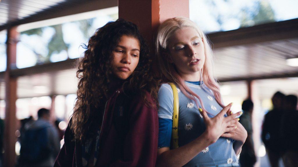 soundtracks de euphoria, séries de tv. Na imagem aparece as personagens Jules e Rue. Rue usa casaco roxo e está ao lado de Jules. Jules usa uma blusa azul florida, cabelo loiro e bolsa amarela.
