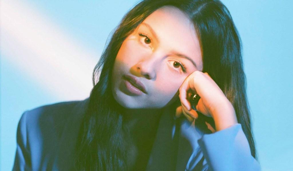 """A foto apresenta a cantora Olivia Rodrigo com seus cabelos pretos. Ela usa um terno iluminada por um feixe azul. É possível ver seu rosto levemente inclinado para a direita. Seus olhos e seu nariz estão iluminados com um feixe alaranjado. Sua boca está pintada com um batom rosa e seu braço esquerdo está apoiado em seu rosto. A foto destaca a matéria: """"""""Sour"""": álbum de Olivia Rodrigo já bateu recordes! Confira"""""""