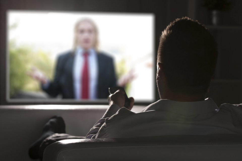 Man watching TV on couch.