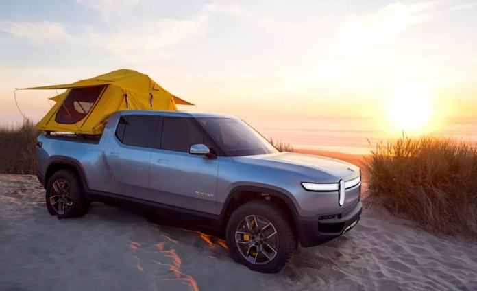 rivian r1t all electric pickup truck on the beach sunset