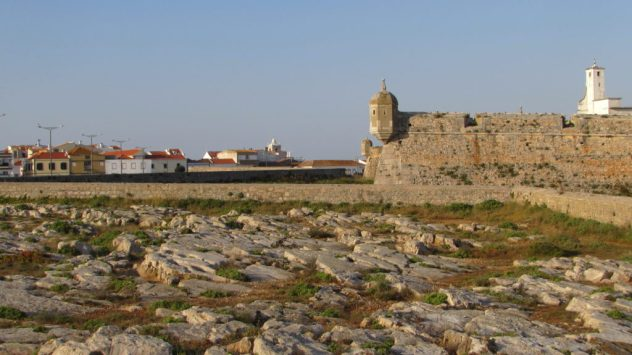 Exposed limestone at Peniche dating from the Jurassic period with the Fortaleza de Peniche in the background