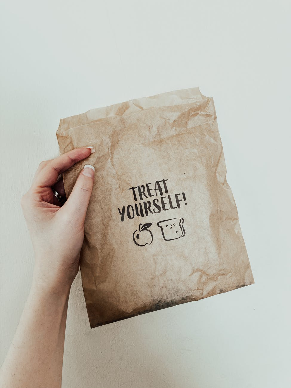 crop faceless woman showing paper bag against white wall