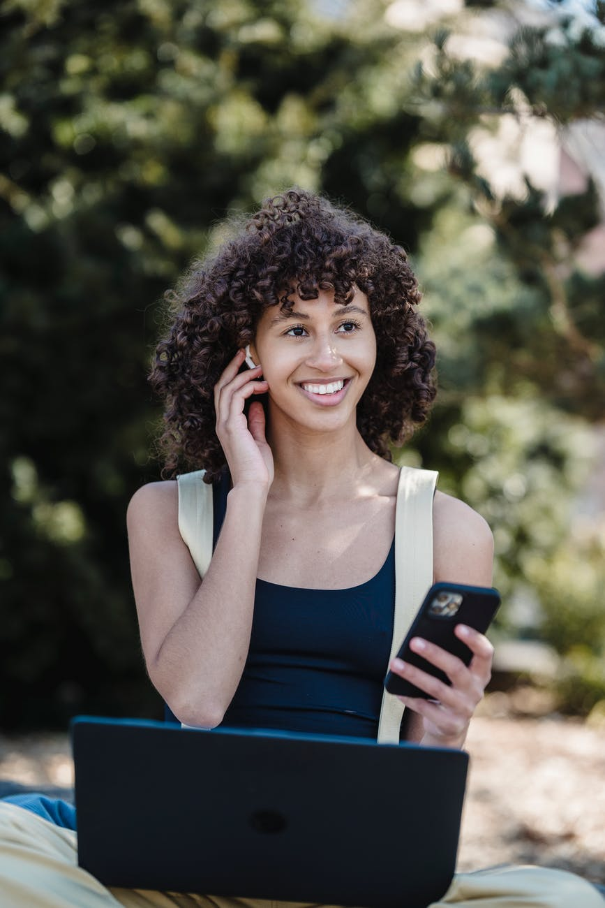 smiling ethnic woman with smartphone working in nature