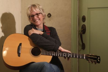 Photo of Tracy Newman seated holding her guitar on the front porch of her home (Photo by Jeff Fasano)