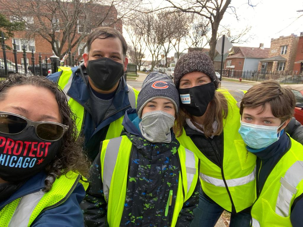 Five people pose for a picture wearing masks, winter caps and yellow safety vests.