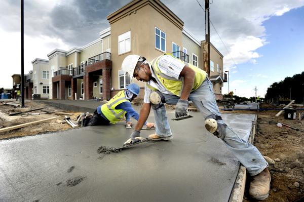 Pierson Concrete workers Beein Castillo, right, and Odell Swecker work on a concrete sidewalk Wednesday at the Violet Crossing development at 13th Street and Violet Avenue in north Boulder. A proposed change to Boulder's land use code would allow developers to make their density calculations before setting aside land for roads. (Jeremy Papasso/Daily Camera)