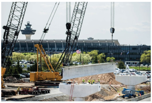 Construction workers with Capital Rail Constructors lift a 2,000-pound girder into place on the Dulles extension of the Silver Line of the Metro last month. (Pete Marovich For The Washington Post)