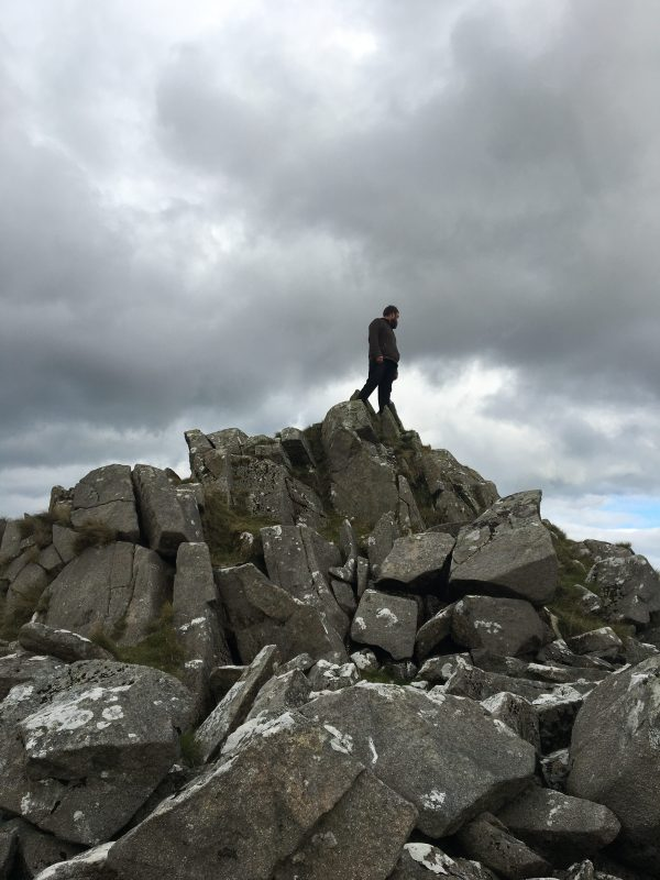 Man standing on rocky outcrop looking over the Valley
