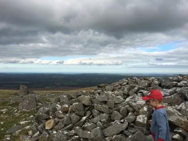 Boy scrambling over rocky outcrop