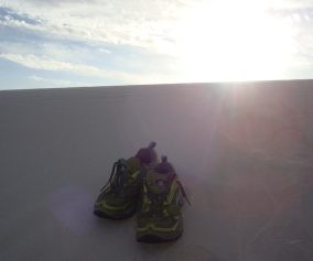 Running shoes in the dunes with sun in the background