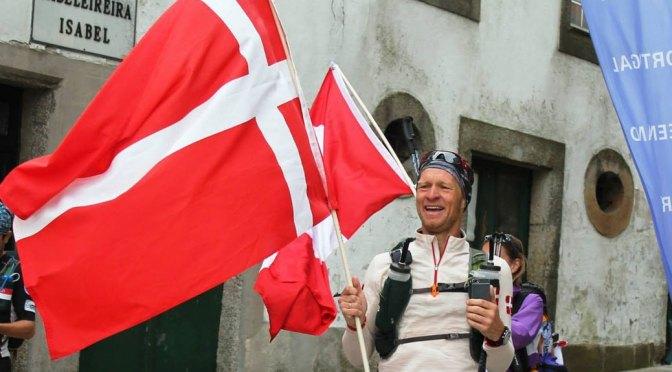 En meget glad Carsten Nøhr Nielsen kort før mål ved Crossroads 2015. Han har et stort Dannebrogsflag i den ene hånd og en mobiltelefon i den anden.