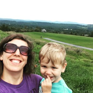 Mother and son on a green hilltop