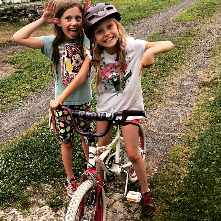 Two girls making funny faces, one on a bicycle