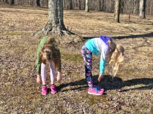Two girls in a park demonstrating the standing forward bend stretch