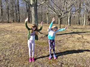 Two children in a park demonstrating side stretches