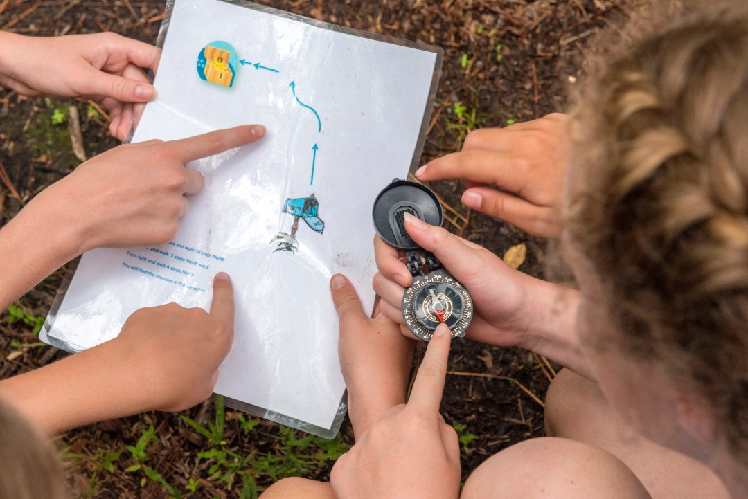 Girls outdoors using map and compass