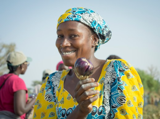 A woman shows off her freshly harvest eggplant