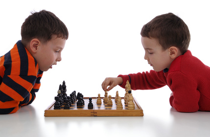 Two little boys playing chess
