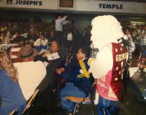 """George the Colonial"" gives his autograph to Bill Cosby during the 1996 Atlantic-10 basketball tournament"