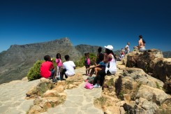 A group of people on top of Lions head in cape town, with table mountain behind them