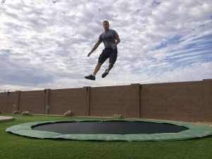 adult bouncing on in ground trampoline