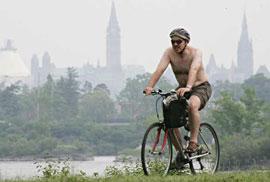 En man är ute och cyklar en dag med myckt smog och föroreningar i luften