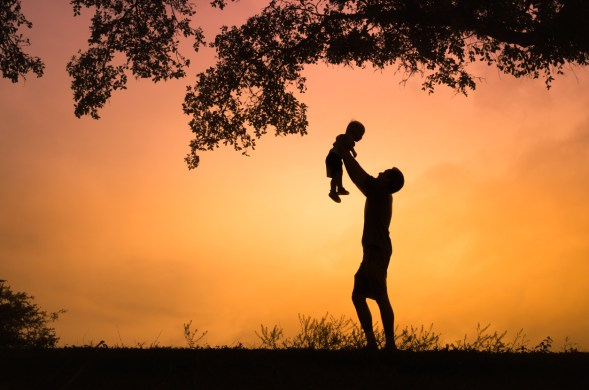 Father holding up son toward the sky as if surrendering a prodigal child