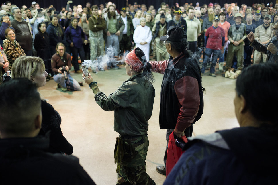 U.S. Army Veterans Tih Kobolson, left, and Aloysious Bell, walk around with a ceremonial smudge stick and feathers during a forgiveness ceremony at the Four Prairie Knights Casino & Resort on the Standing Rock Sioux Reservation on Monday, Dec. 5, 2016.