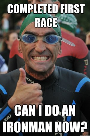 Man in goggles and wetsuit giving thumbs up and smiling during first triathlon.