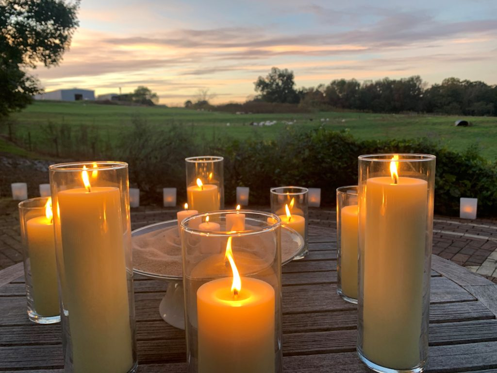 candles in front of a field at sunset