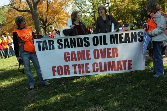 protesters with anti-tar sands banner