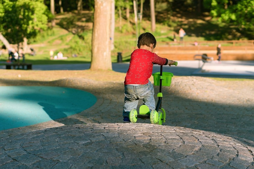 Toddler riding scooter at park
