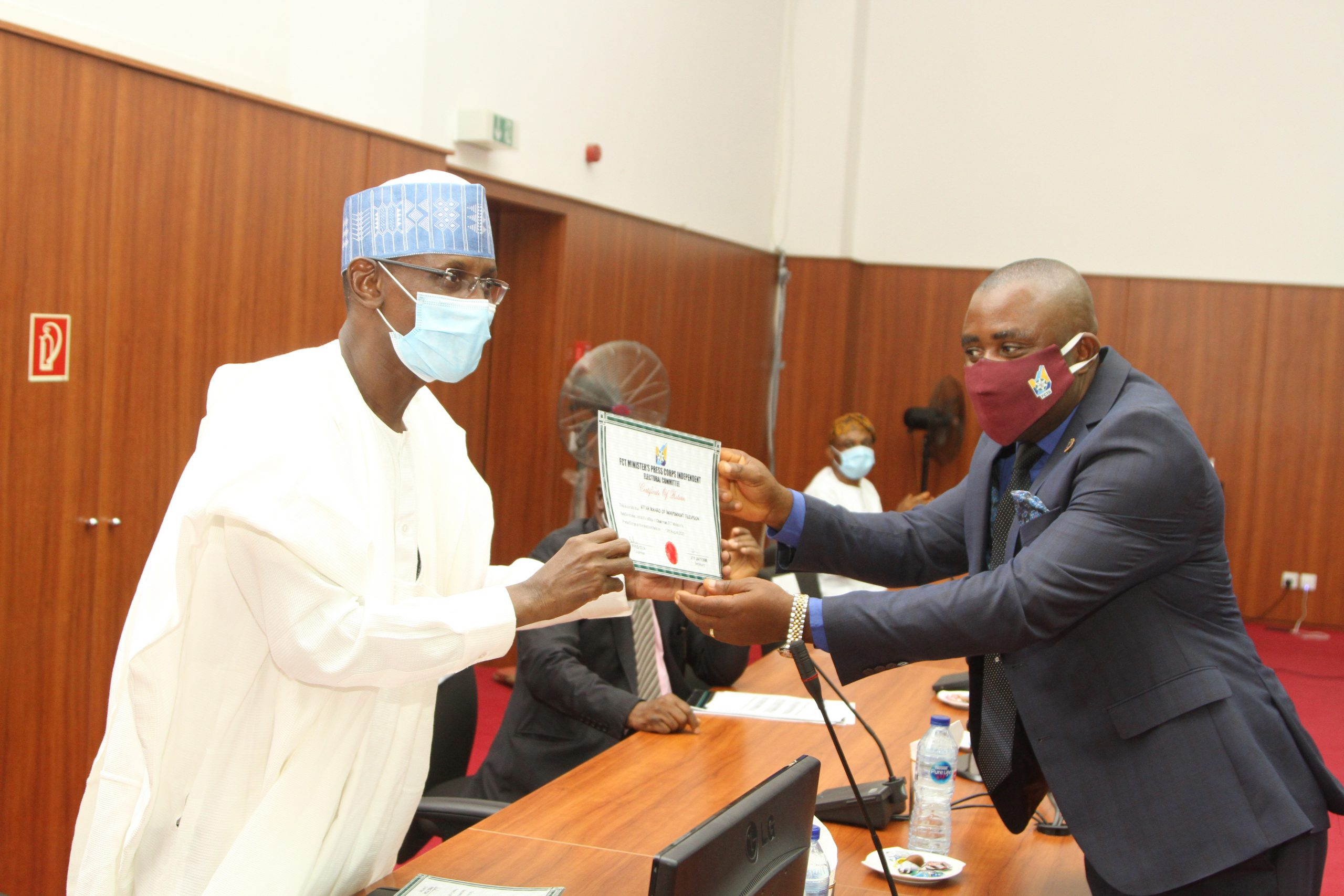 FCT Minister, Malam Muhammad Musa Bello presenting the Certificate of Return to Ikharo Attah, Chairman, FCT Minister's press Corps following the Swearing-in ceremony of the new EXCO yesterday in Abuja.