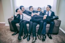 Australian groom and his groomsmen laugh on the sofa