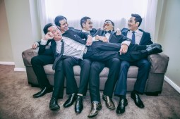 Australian groom and his groomsmen laugh on the sofa
