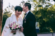 Australian and asian wedding couple as the groom kisses bride's head